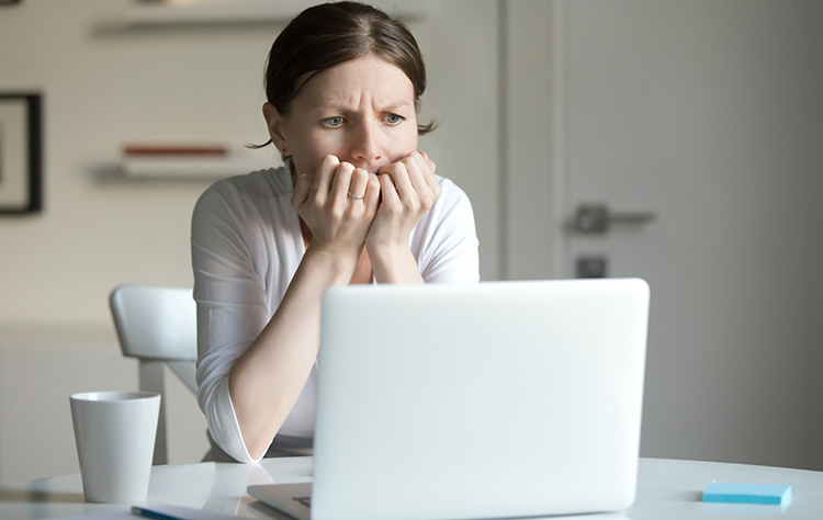 Portrait of a young woman at desk with laptop, fear